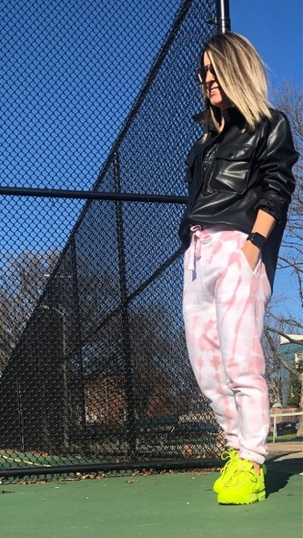 Woman wearing sunglasses, leather jacket, yellow sneakers, and pink tie dye joggers standing on tennis court with hands in pockets