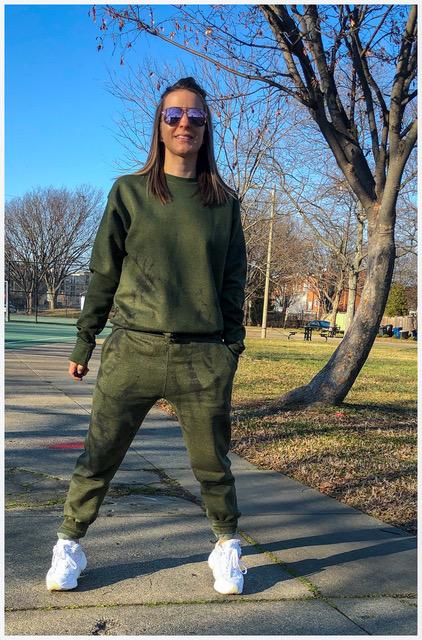 Woman wearing DIY tie dye matching sweatsuit in sunglasses and sneakers on sidewalk