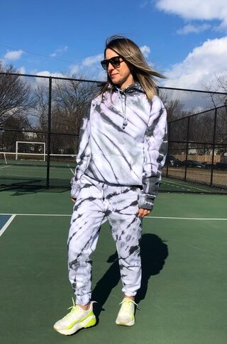 Woman wearing DIY tie dye matching sweatsuit in sunglasses and sneakers on tennis court